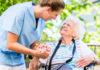 Krankenpflegerin mit älterer Dame in Seniorenheim